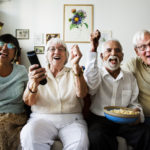 Group Of Cheerful Senior Friends Sitting And Watching TV Together